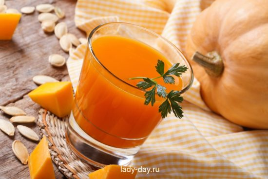 Pumpkin juice with pulp close-up on a table on a background of ripe vegetable