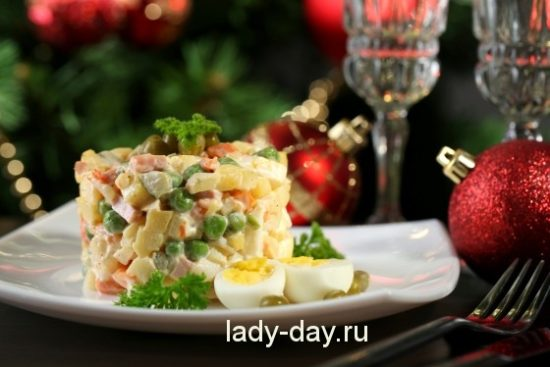 Russian traditional salad Olivier, on wooden table, on bright background